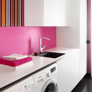 Immagine di una sala lavanderia design di medie dimensioni con lavello a vasca singola, ante lisce, ante bianche, pareti rosa, lavatrice e asciugatrice affiancate, top in laminato e pavimento nero