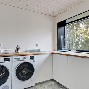 Photo of a large scandi l-shaped separated utility room in Stockholm with a single-bowl sink, white cabinets, wood worktops, white walls, marble flooring and a side by side washer and dryer.