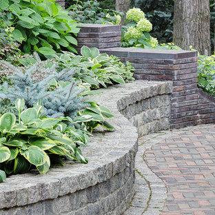 На фото: участок и сад в стиле рустика с подпорной стенкой и мощением клинкерной брусчаткой с