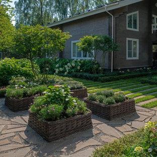 Mittelgroßer, Halbschattiger Klassischer Garten im Sommer, hinter dem Haus mit Natursteinplatten und Hochbeet in Moskau