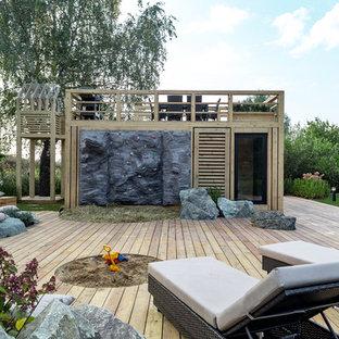 На фото: участок и сад в современном стиле с детским городком с
