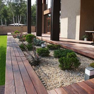 Aménagement d'un jardin avec une terrasse en bois ou composite scandinave l'été.