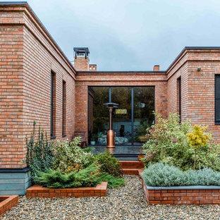 Идея дизайна: солнечный участок и сад в классическом стиле с покрытием из гравия, растениями в контейнерах и освещенностью