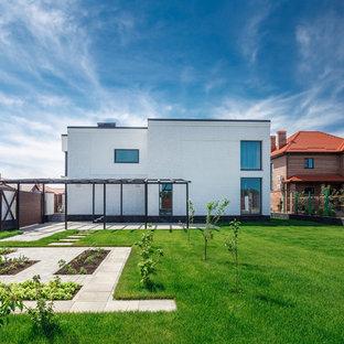 На фото: солнечные, летние, геометрические огороды на участке на заднем дворе в современном стиле с освещенностью и мощением тротуарной плиткой