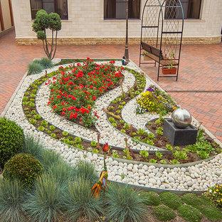 Geometrischer Klassischer Garten im Sommer, hinter dem Haus mit direkter Sonneneinstrahlung, Pflasterklinker und Blumenbeet in Sonstige