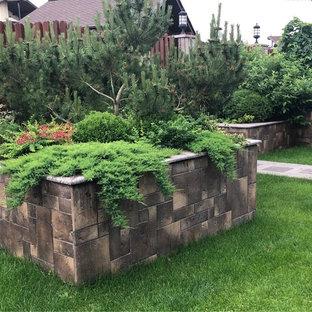 На фото: летний участок и сад в современном стиле с подпорной стенкой и полуденной тенью с