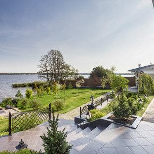 Создайте стильный интерьер: солнечный, летний среднего размера на заднем дворе в классическом стиле с освещенностью и дорожками из брусчатки из камня - последний тренд