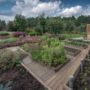 На фото: тенистый, летний огород на участке в классическом стиле с настилом с