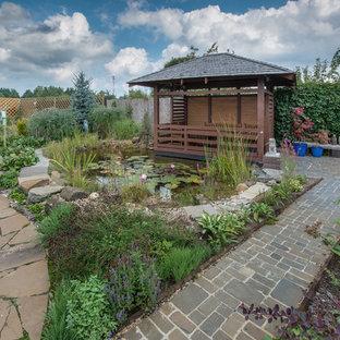 Aménagement d'un jardin classique l'été avec un bassin.