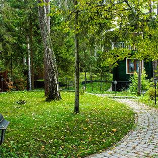 Cette photo montre une allée carrossable scandinave de taille moyenne et l'automne avec une exposition partiellement ombragée, une pente, une colline ou un talus, des pavés en béton et une entrée ou une allée de jardin.