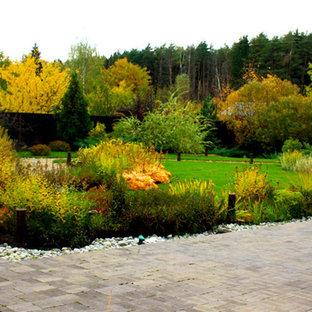 Exemple d'un jardin scandinave de taille moyenne et au printemps avec une exposition ensoleillée, du gravier et un massif de fleurs.