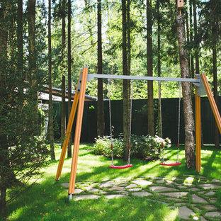 На фото: летний участок и сад в современном стиле с детским городком и полуденной тенью с