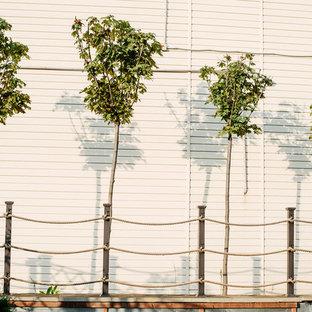 На фото: солнечный, летний участок и сад в морском стиле с освещенностью с