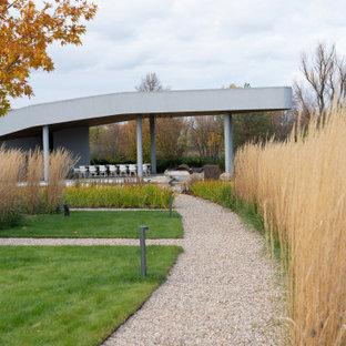 На фото: огромный солнечный, летний участок и сад на внутреннем дворе в стиле модернизм с дорожками, хорошей освещенностью и покрытием из гравия с