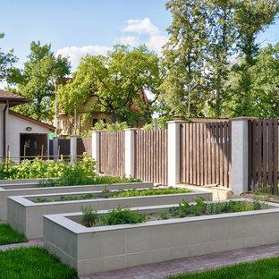 На фото: летний огород на участке на заднем дворе в классическом стиле с полуденной тенью