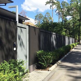 На фото: летний участок и сад на переднем дворе в современном стиле с подъездной дорогой, полуденной тенью и покрытием из каменной брусчатки