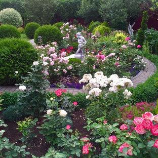 Aménagement d'un jardin à la française arrière classique avec des pavés en brique et un chemin.