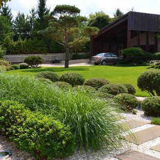 На фото: летний, солнечный участок и сад среднего размера на переднем дворе в стиле модернизм с хорошей освещенностью, покрытием из гравия и садовой дорожкой или калиткой с