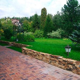 Стильный дизайн: летний, геометрический участок и сад среднего размера на боковом дворе в средиземноморском стиле с подпорной стенкой, полуденной тенью и мощением клинкерной брусчаткой - последний тренд