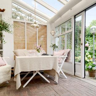 Idée de décoration pour une véranda nordique avec un plafond en verre et un sol marron.