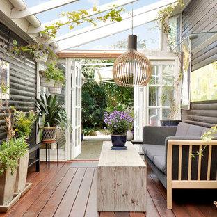 Immagine di una veranda scandinava di medie dimensioni con parquet scuro e soffitto in vetro