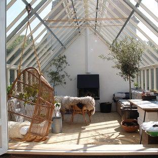 Exemple d'une véranda scandinave avec une cheminée standard, un manteau de cheminée en plâtre et un plafond en verre.