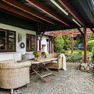 Foto på en mellanstor lantlig uteplats längs med huset, med utekrukor, naturstensplattor och takförlängning