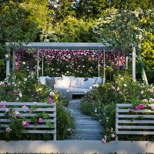 Esempio di un patio o portico country con pedane e una pergola