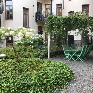 Foto di un patio o portico nordico con ghiaia e una pergola