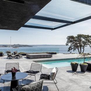 Inspiration för en stor funkis uteplats på baksidan av huset, med betongplatta och takförlängning