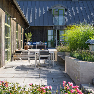 Mid-sized danish backyard stone patio photo in Malmo with no cover