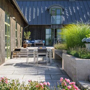 Idéer för mellanstora minimalistiska uteplatser på baksidan av huset, med naturstensplattor