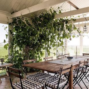 Aménagement d'une grand véranda romantique avec un sol en carreau de terre cuite, un sol orange et un plafond standard.