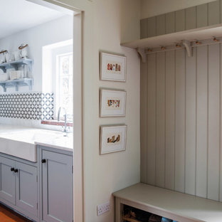 Inspiration for a small country galley dedicated laundry room in Kent with a farmhouse sink, granite benchtops, terra-cotta floors, a side-by-side washer and dryer, orange floor, beaded inset cabinets, blue cabinets, white walls and white benchtop.