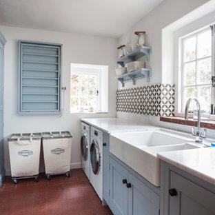 ケントの小さいカントリー風おしゃれな洗濯室 (エプロンフロントシンク、青いキャビネット、御影石カウンター、白い壁、テラコッタタイルの床、左右配置の洗濯機・乾燥機、シェーカースタイル扉のキャビネット、赤い床、白いキッチンカウンター) の写真