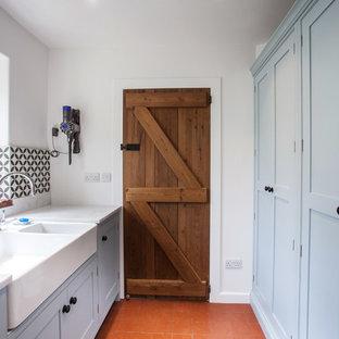 Foto di una piccola sala lavanderia country con lavello stile country, ante con riquadro incassato, ante blu, top in granito, pareti bianche, pavimento in terracotta, lavatrice e asciugatrice affiancate, pavimento arancione e top bianco
