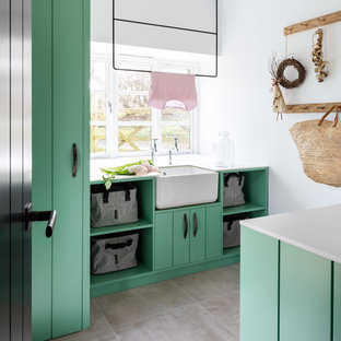 This is an example of a country laundry room in Gloucestershire with flat-panel cabinets, green cabinets, white benchtop, a farmhouse sink, white walls and grey floor.