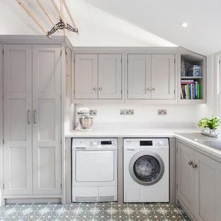 Foto di una piccola sala lavanderia tradizionale con lavello a vasca singola, ante a filo, ante grigie, top in quarzite, pareti bianche, pavimento con piastrelle in ceramica, lavatrice e asciugatrice affiancate e pavimento multicolore