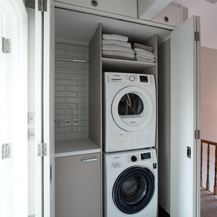 Small contemporary single-wall laundry cupboard in London with flat-panel cabinets, brown cabinets, a stacked washer and dryer, black floors and white worktops.