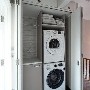 Exemple d'une petit buanderie linéaire tendance avec un placard, un placard à porte plane, des portes de placard marrons, des machines superposées, un sol noir et un plan de travail blanc.