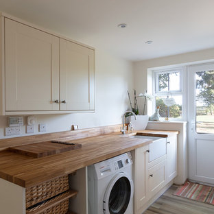 Medium sized traditional single-wall separated utility room in Berkshire with a belfast sink, shaker cabinets, beige cabinets, wood worktops, beige walls, brown floors and brown worktops.
