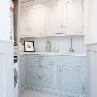 Immagine di una piccola lavanderia multiuso country con lavello integrato, ante lisce, ante blu, top in quarzite, pareti bianche, pavimento con piastrelle in ceramica, lavatrice e asciugatrice a colonna, pavimento bianco e top bianco