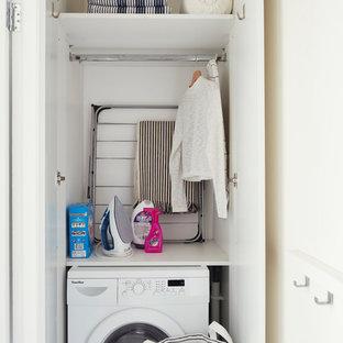 Idéer för att renovera en liten minimalistisk linjär liten tvättstuga med garderob, med släta luckor, vita skåp, vita väggar, vinylgolv och vitt golv