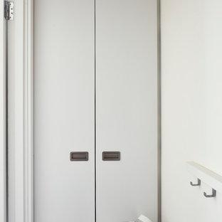 Esempio di un piccolo ripostiglio-lavanderia design con ante lisce, ante bianche, pareti bianche, pavimento in vinile, lavasciuga e pavimento bianco