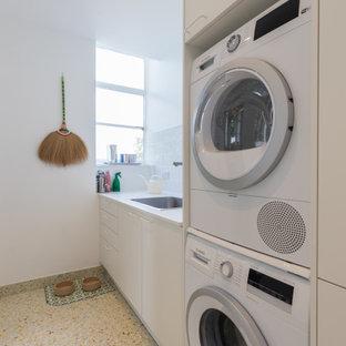 Idee per una grande sala lavanderia design con lavello da incasso, ante lisce, ante bianche, top in superficie solida, paraspruzzi bianco, paraspruzzi con piastrelle in ceramica, pareti bianche, pavimento in gres porcellanato, lavatrice e asciugatrice a colonna, pavimento verde e top bianco