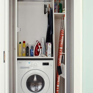Design ideas for a small contemporary utility room in Dublin with flat-panel cabinets, white cabinets and white walls.
