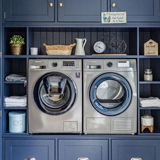 Foto på en vintage tvättstuga, med luckor med profilerade fronter, blå skåp, en tvättmaskin och torktumlare bredvid varandra och flerfärgat golv
