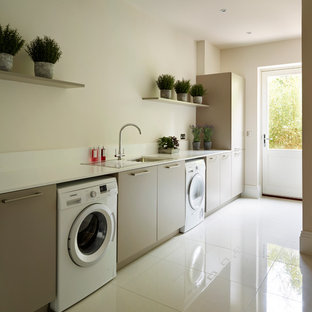 Trendy single-wall white floor laundry room photo in Essex with flat-panel cabinets, a side-by-side washer/dryer, beige walls, gray cabinets and a drop-in sink
