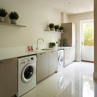 Idée de décoration pour une buanderie linéaire design avec un placard à porte plane, des machines côte à côte, un mur beige, un sol blanc, des portes de placard grises et un évier posé.