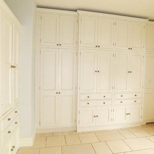 Inspiration för mellanstora klassiska parallella grovkök, med en rustik diskho, luckor med infälld panel, vita skåp, granitbänkskiva, vita väggar, kalkstensgolv och tvättmaskin och torktumlare byggt in i ett skåp